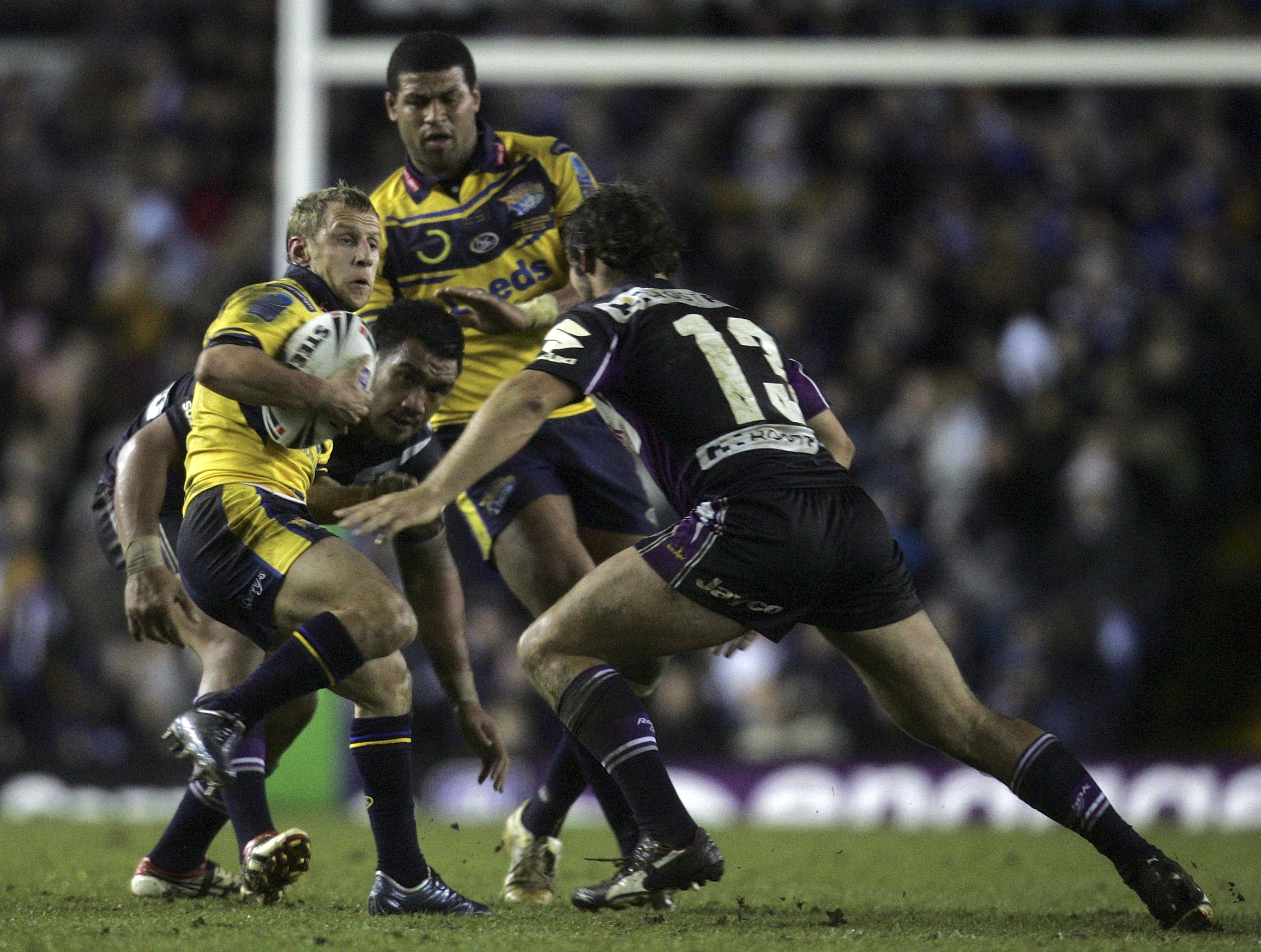 Leeds Rhinos' Rob Burrows, left, tries to evade the tackle of Melbourne Storm's Dallas Johnson, right, during their World Club Challenge, Rugby League...