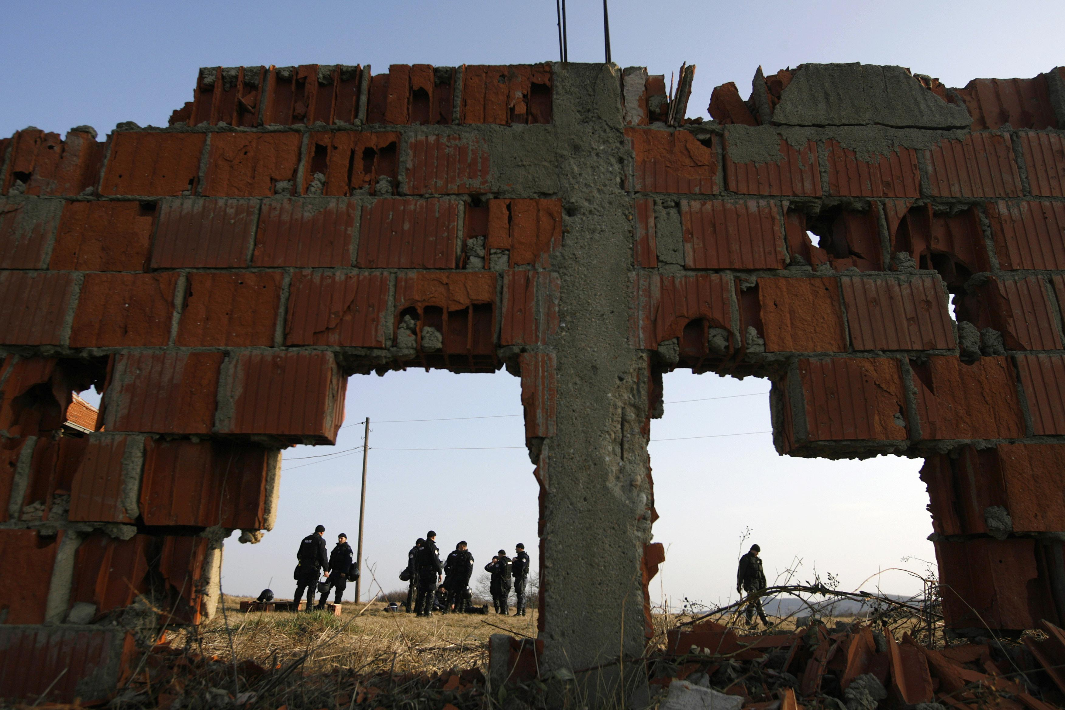 Kosovo riot policemen are seen on Thursday through a damaged wall as they