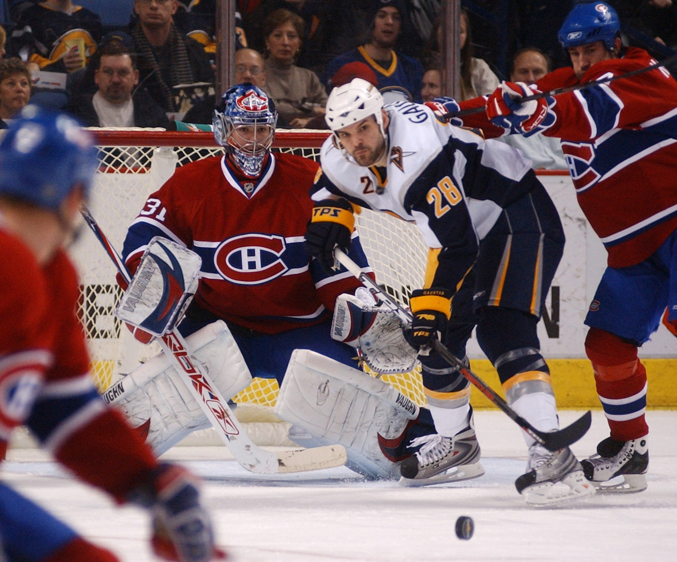 Montreal Canadiens goaltender Carey Price, left, keeps his eye on an incoming puck along with Buffalo Sabres center Paul Gaustad, second right, during...
