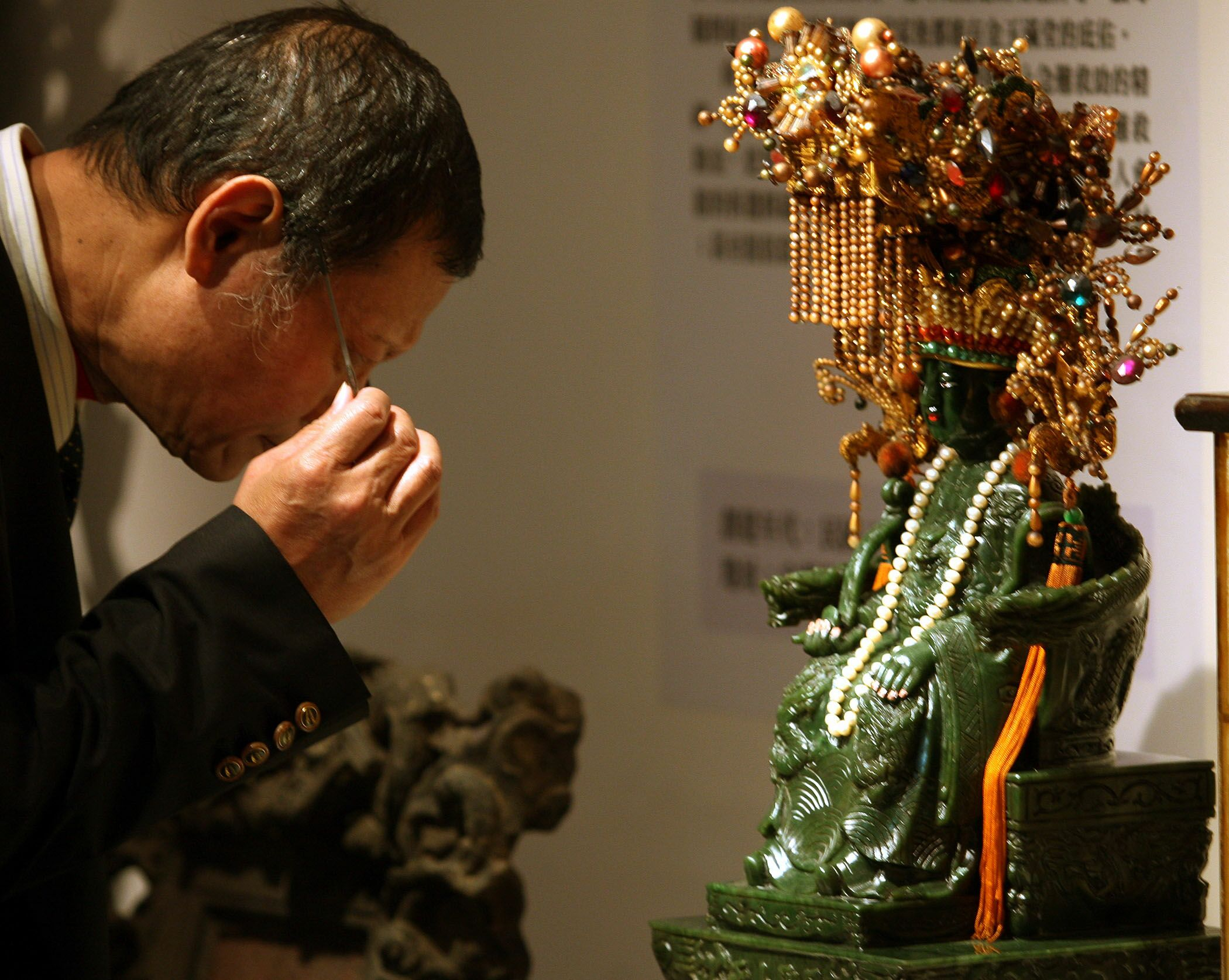 A visitor carefully reads information about a Ma Zu statue at the National Museum of History exhibition.