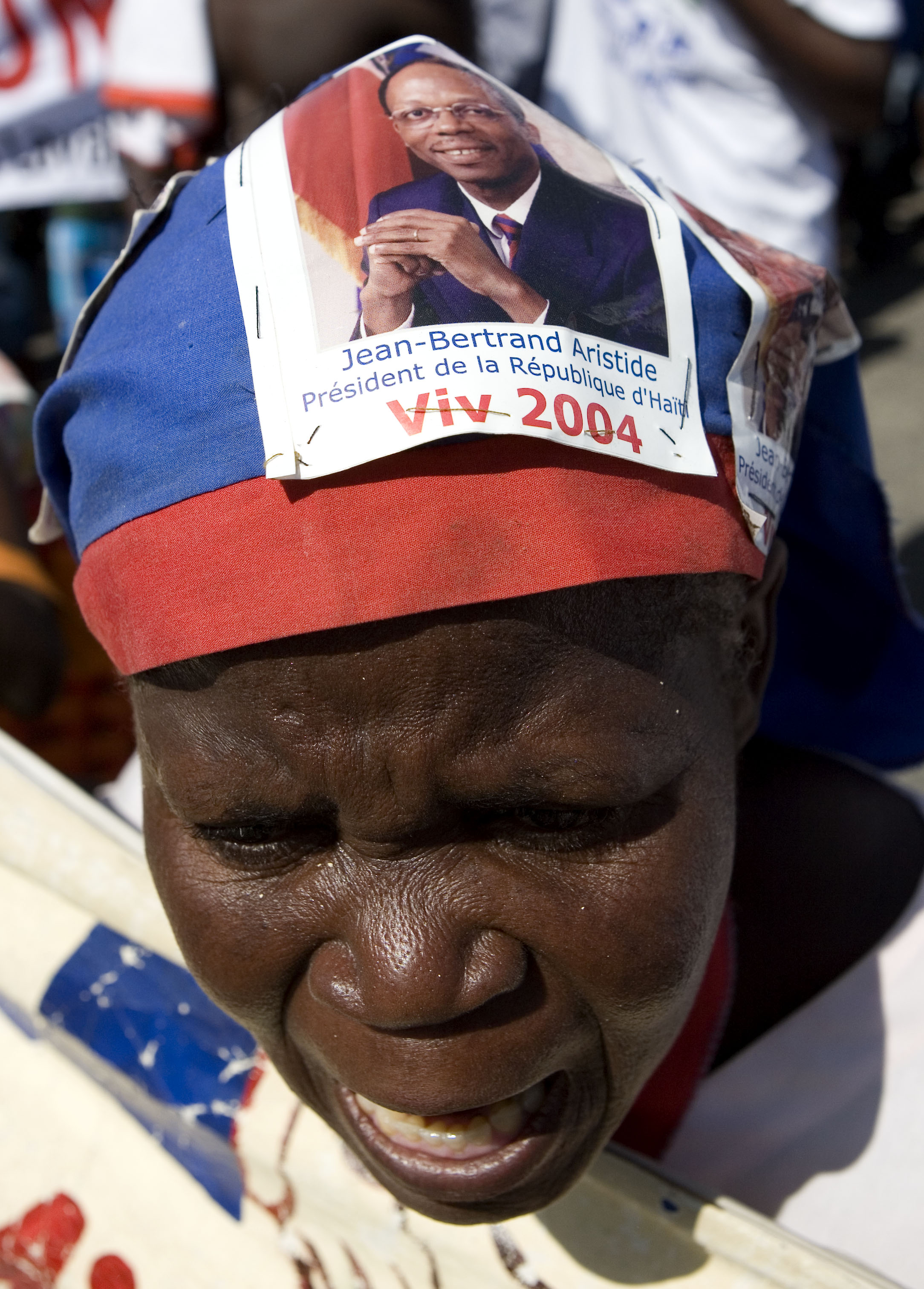 A supporter of  former Haitian President Jean Bertrand Aristide sings in Port-au-Prince, Haiti, during a demonstration demanding the return of Aristid...