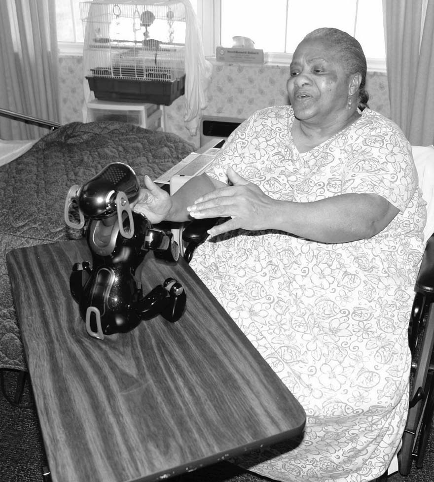 In this 2006 file photo provided by Saint Louis University in Missouri, resident Gladys Moore is seen playing with robotic dog AIBO.