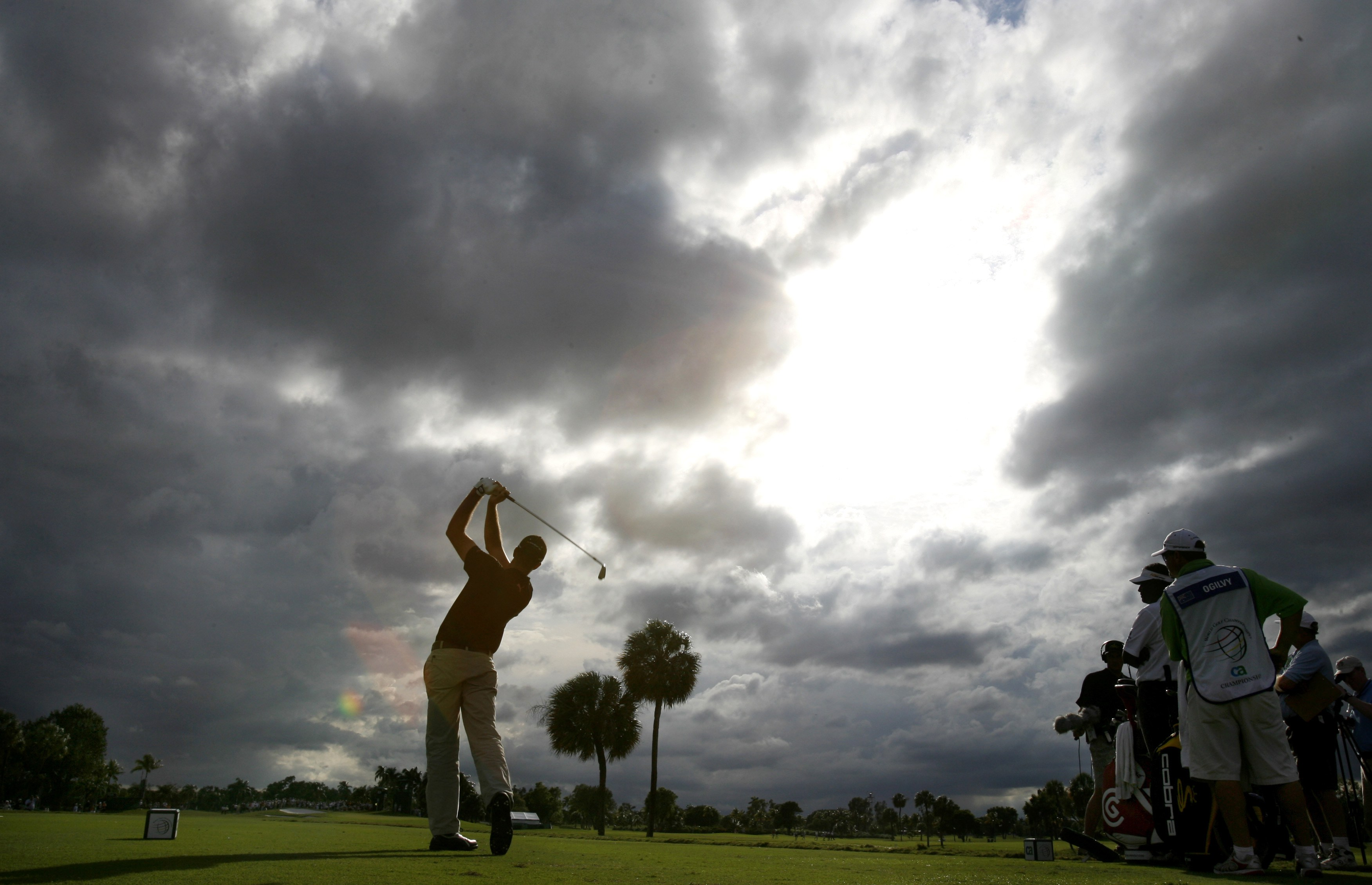Geoff Ogilvy of Australia watches his tee shot on the fourth hole under threatening storm clouds during final round of the WGC-CA Championship golf to...