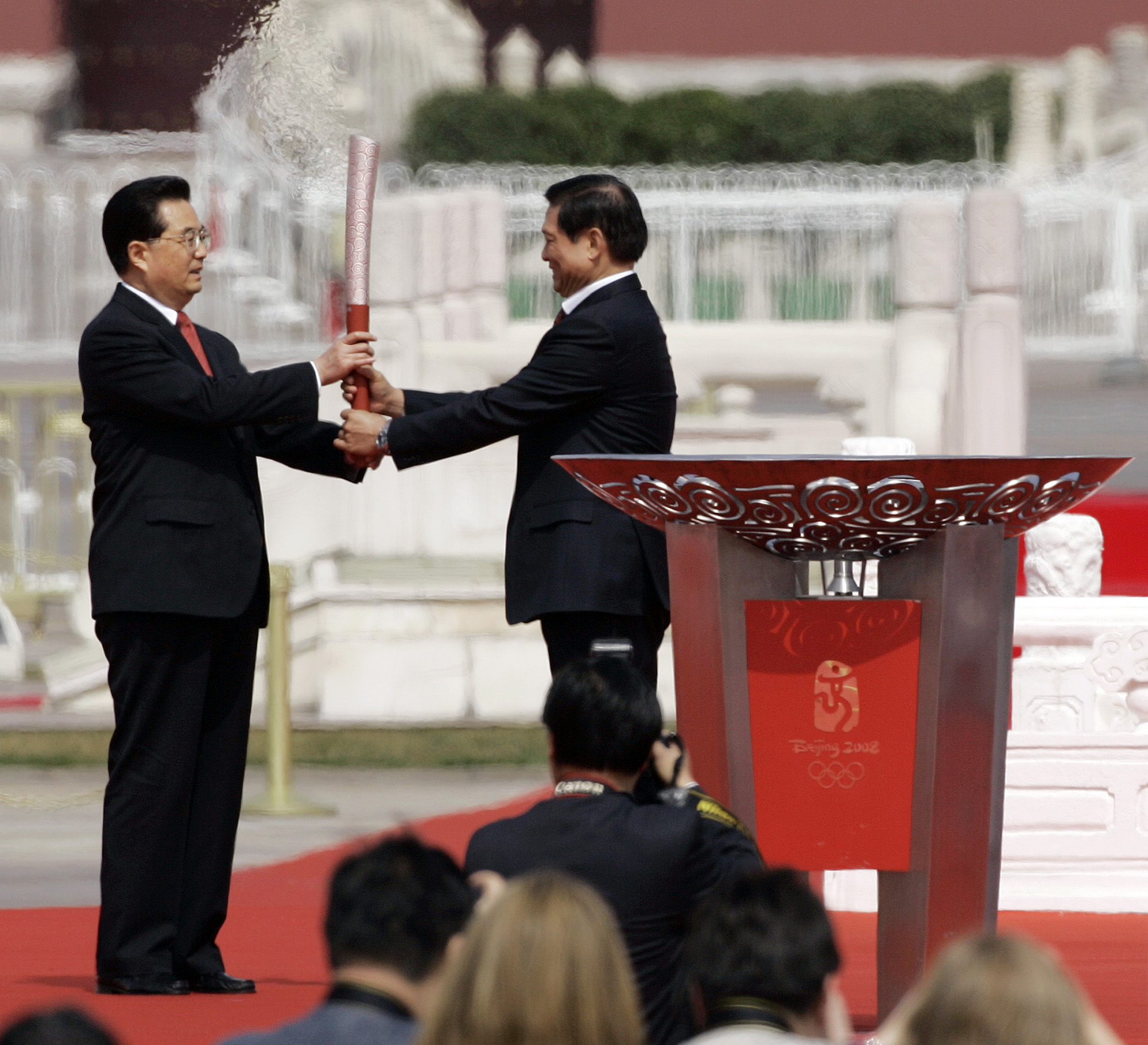 Chinese President Hu Jintao, left, receives the Olympic torch from Liu Qi, the president of the Beijing Olympics organizing committee, during the Beij...