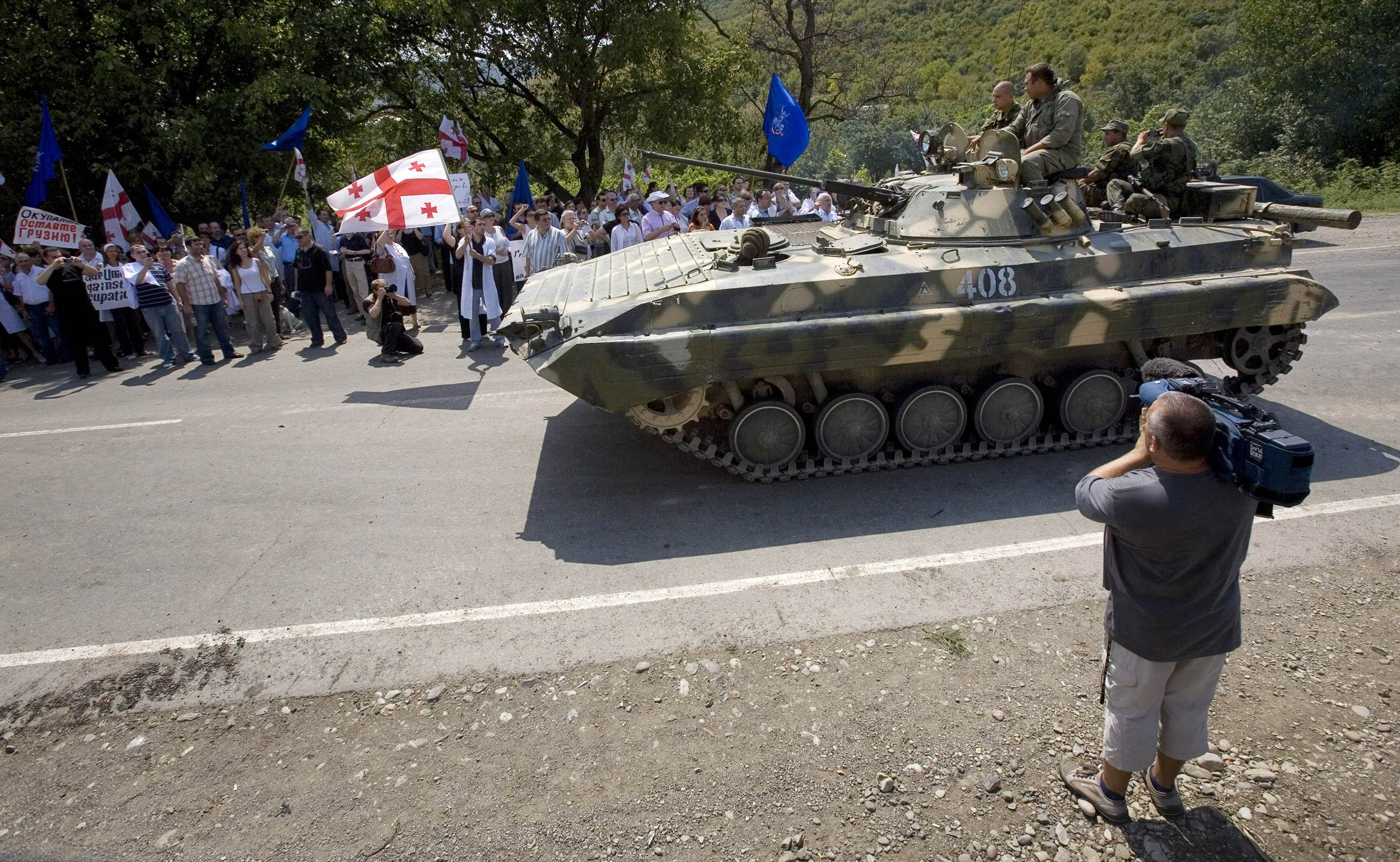 Georgians confront Russian soldiers at a checkpoint as a Russian amored personnel carrier passes on the road from Tbilisi to Gori, Georgia yesterday....