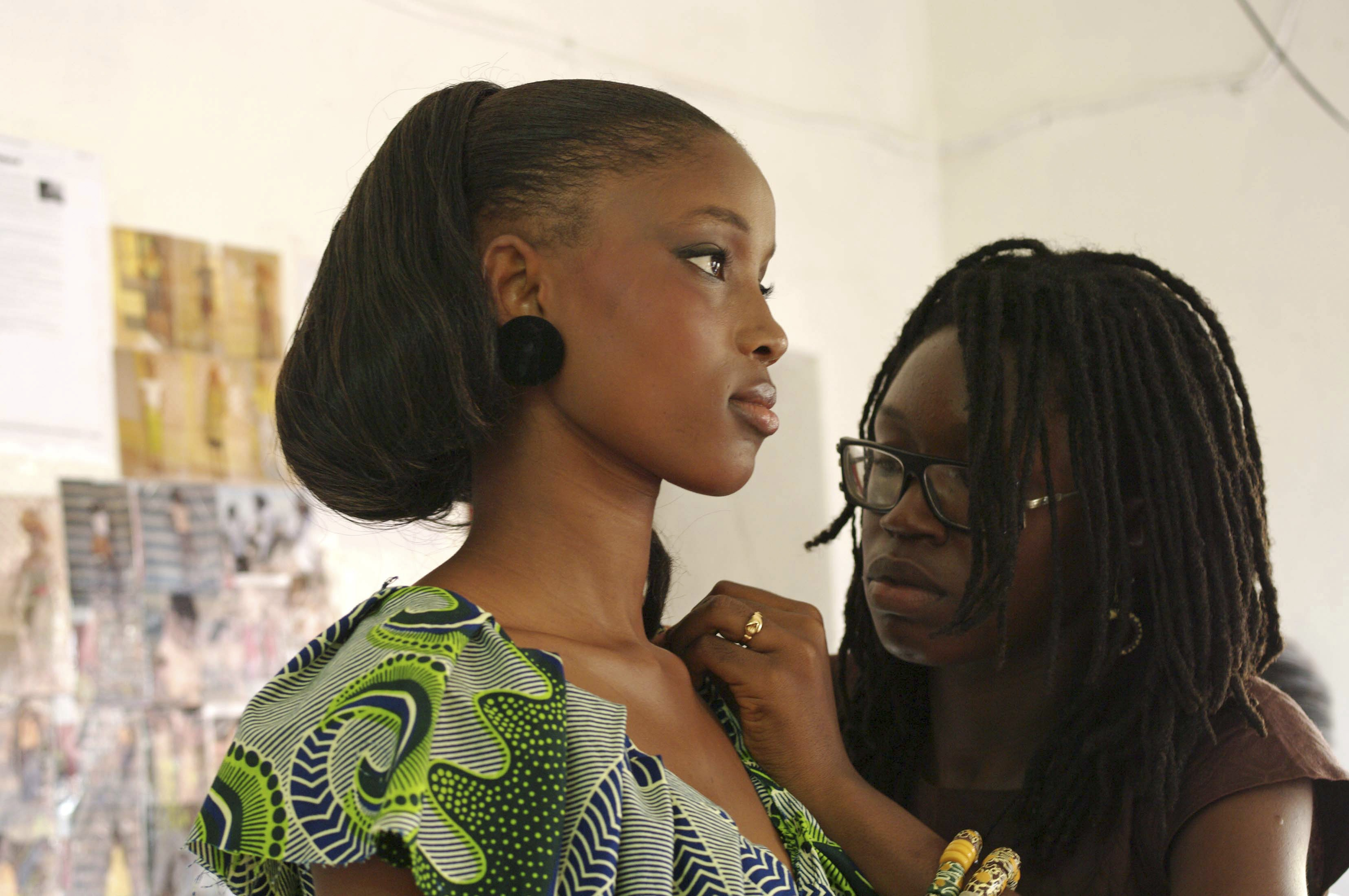 Sierra Leonean fashion designer Adama Kai, right, adjusts a dress on Ramatu Wurie during her first photo shoot in downtown Freetown, Sierra Leone on A...