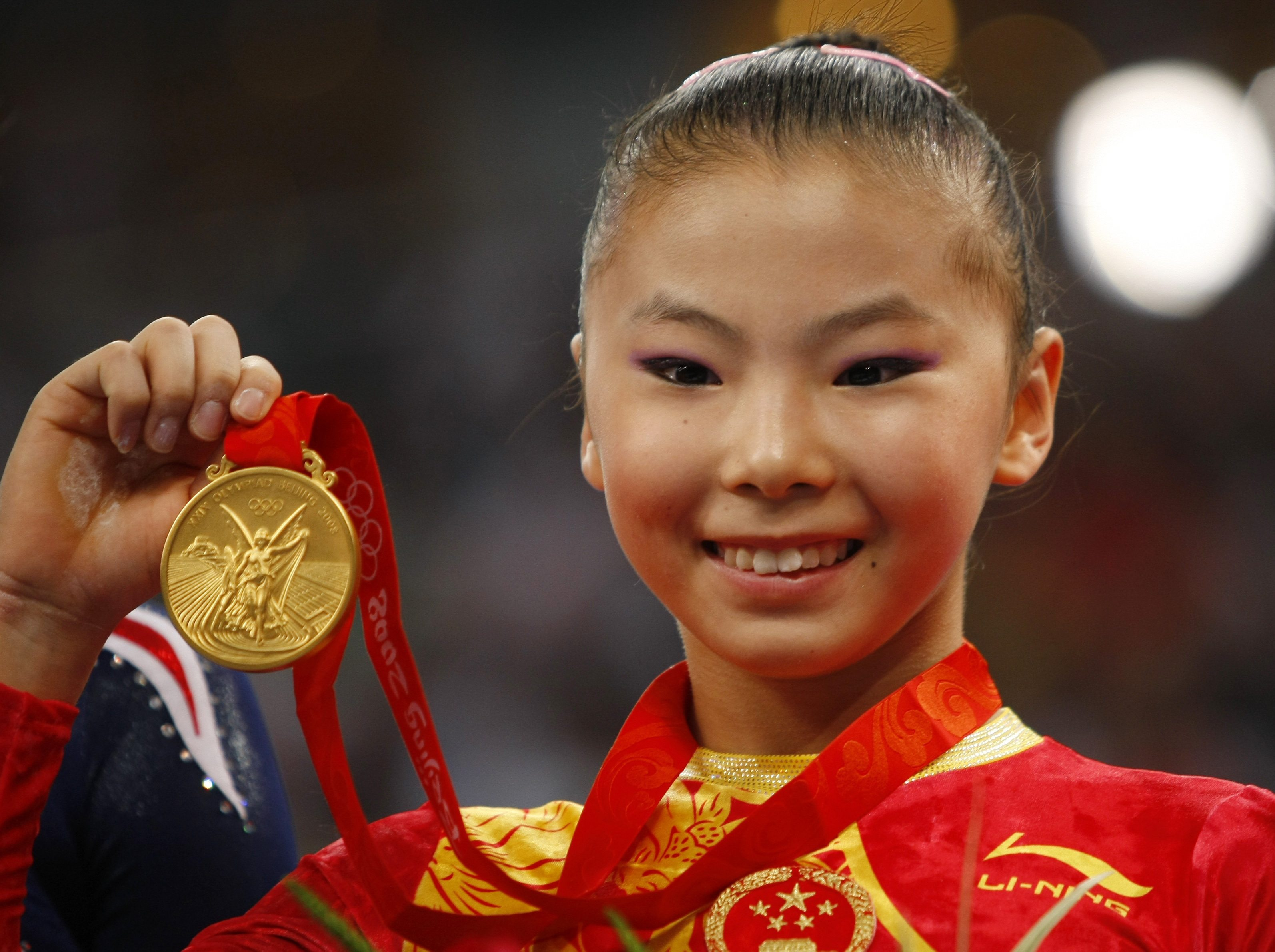 He Kexin of China holds her gold medal during the medal ceremony for the women's uneven bars final in the artistic gymnastics competition at the Beiji...