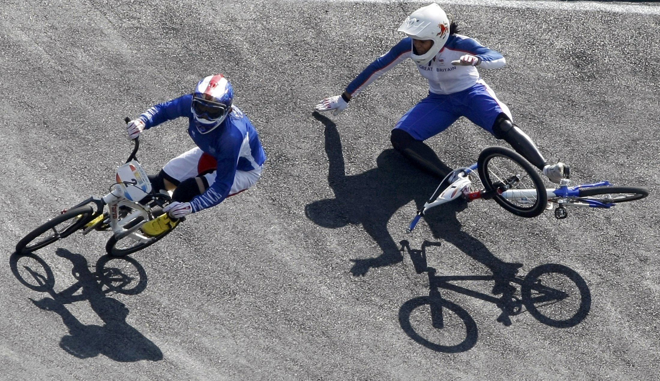 Anne-Caroline Chausson, left, of France takes the lead as Shanaze Reade of Britain falls during the women's final run.