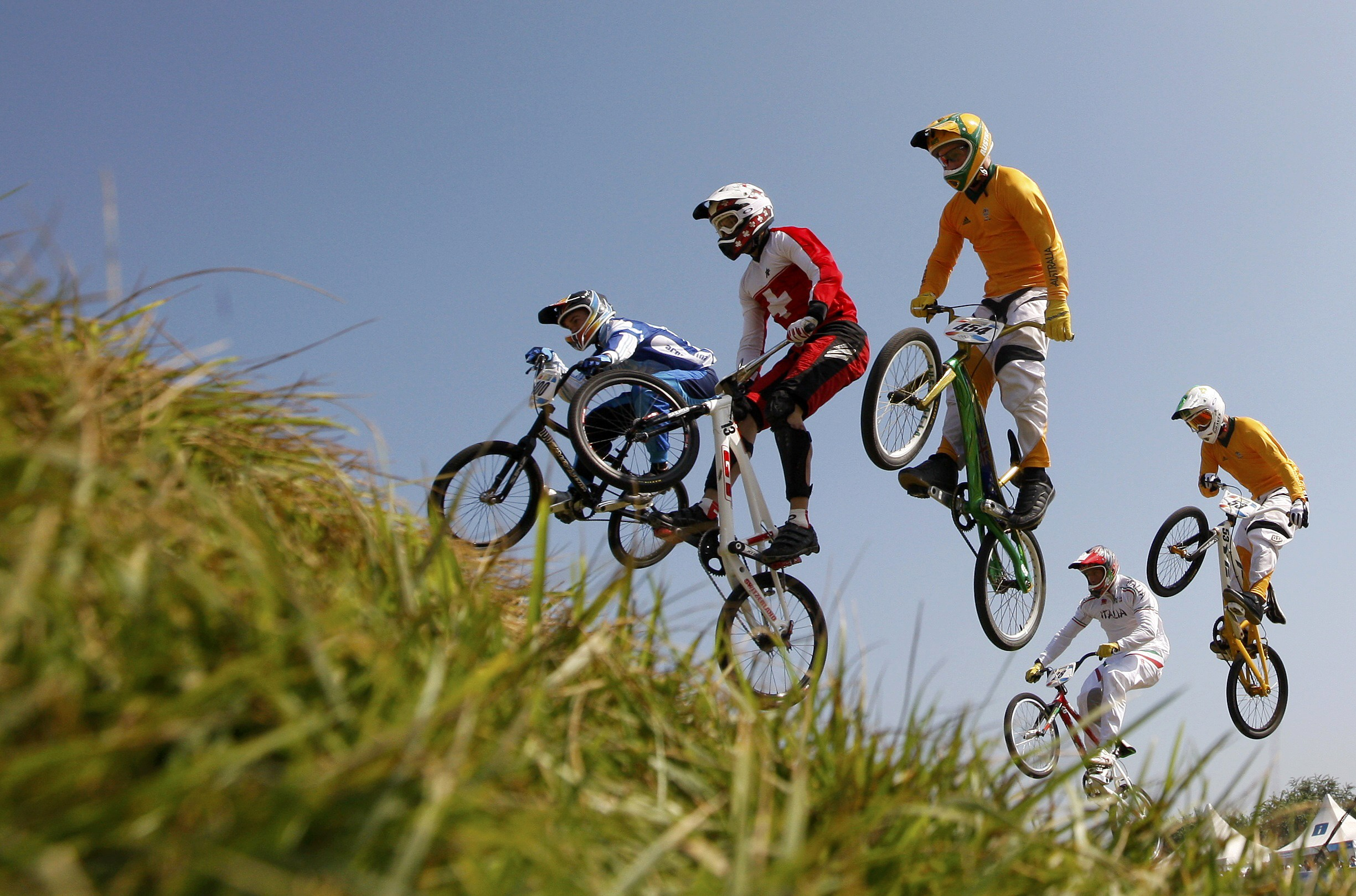 Competitors jump during the men's semifinal run for the BMX  competition at the Beijing 2008 Olympic Games yesterday.