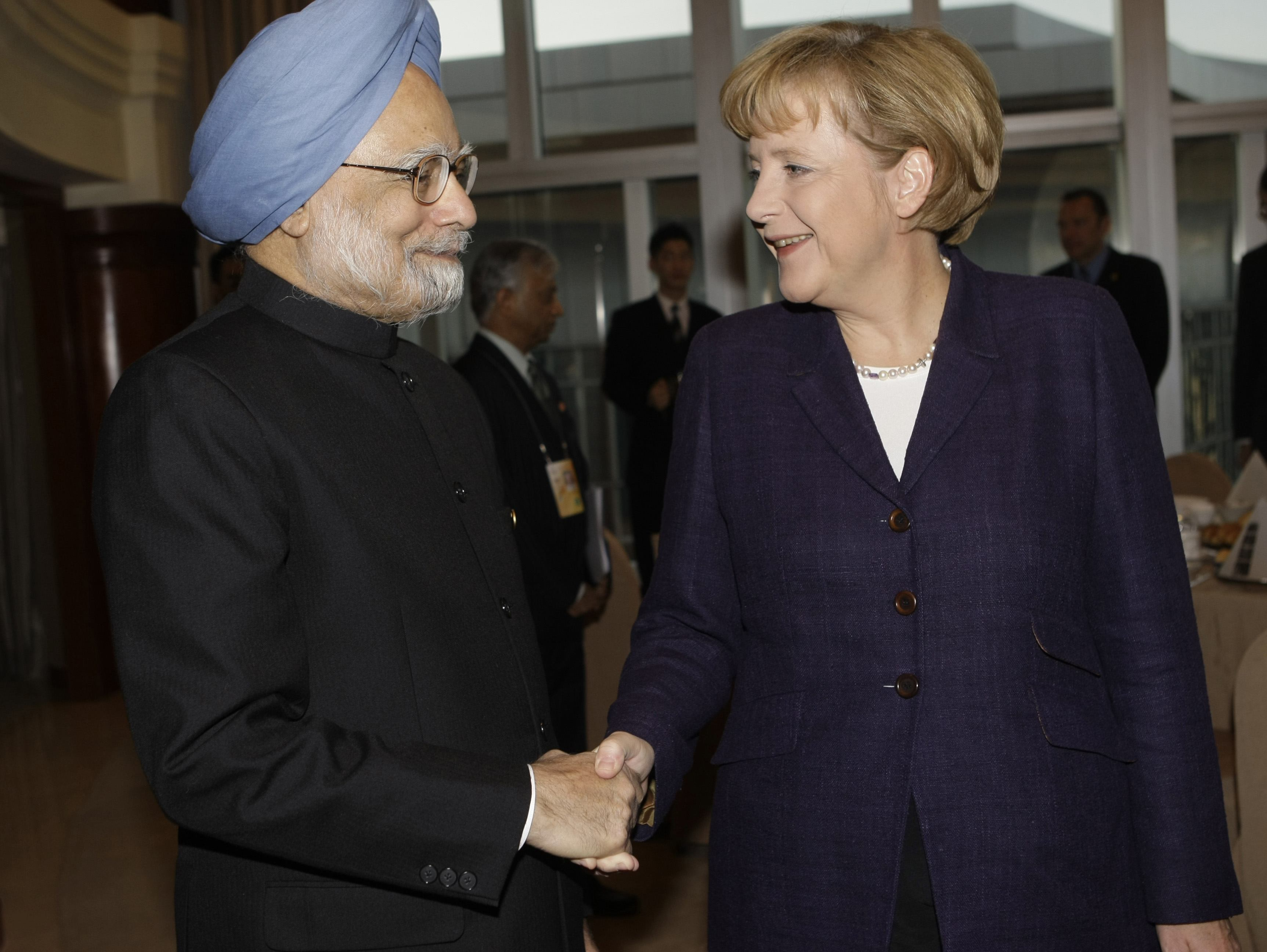India's Prime Minister Manmohan Singh, left, shakes hands with German Chancellor Angela Merkel before a breakfast at a hotel during the Asia-Europe Me...