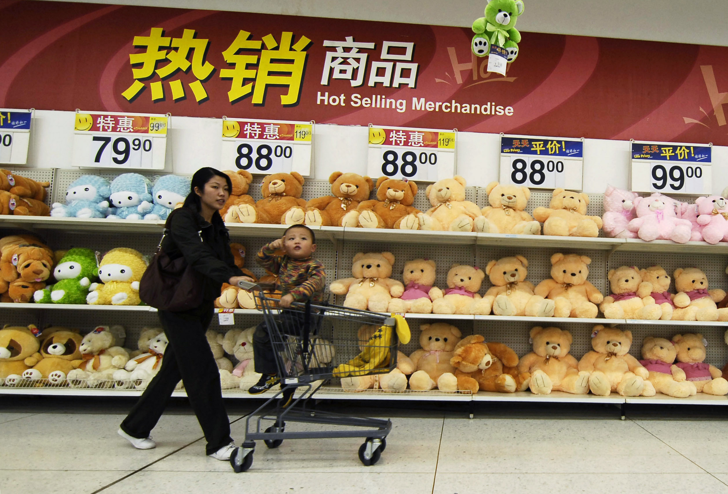 A woman pushes a shopping cart with her child past toys on sale at a supermarket in Xiangfan, Hubei province, China yesterday. China is raising export...