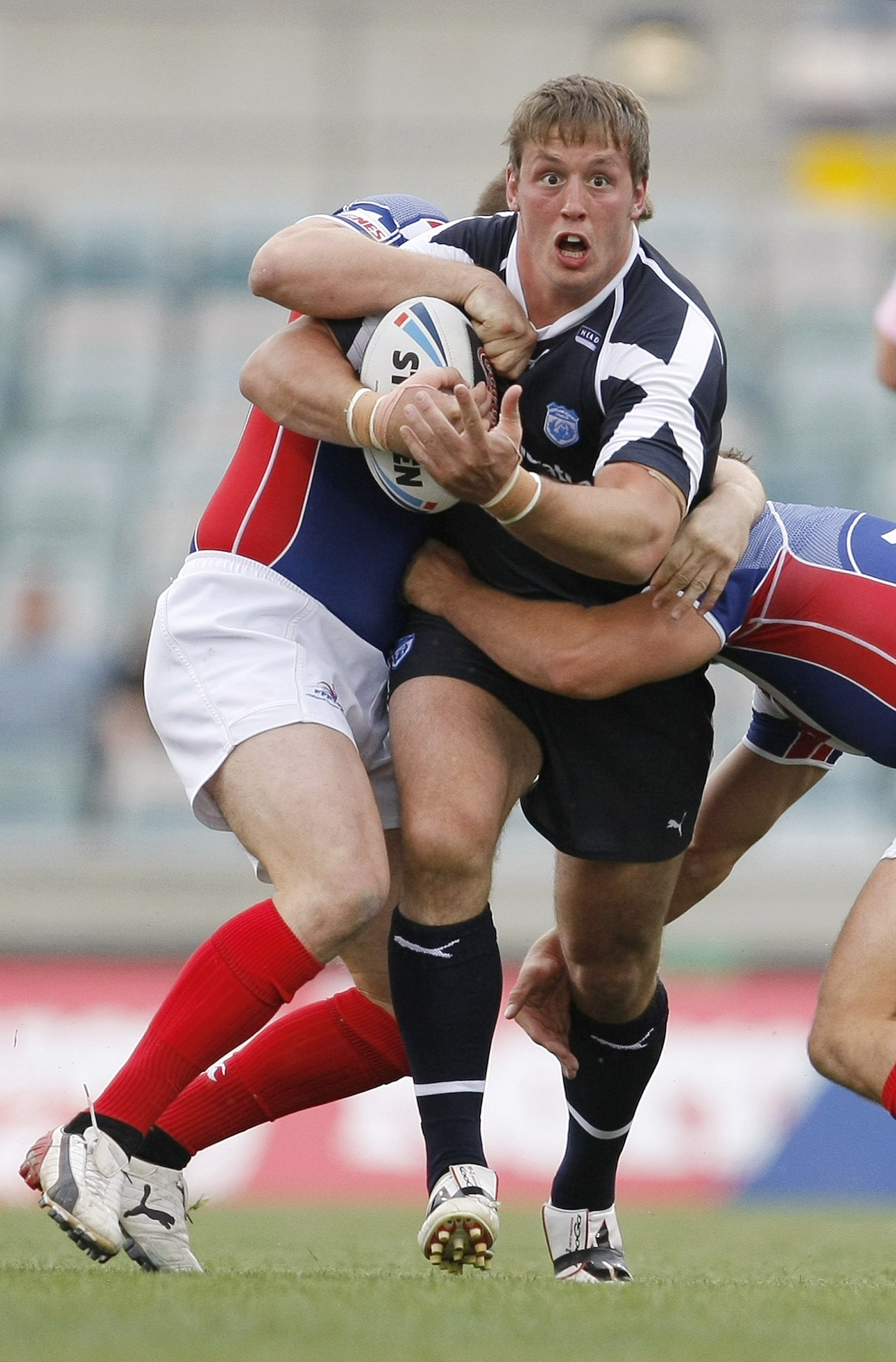 Scotland's Oliver Wilkes tries to escape the tackle of France's Remi Casty, left, and Gregory Mounis during their Rugby League World Cup match at Canb...