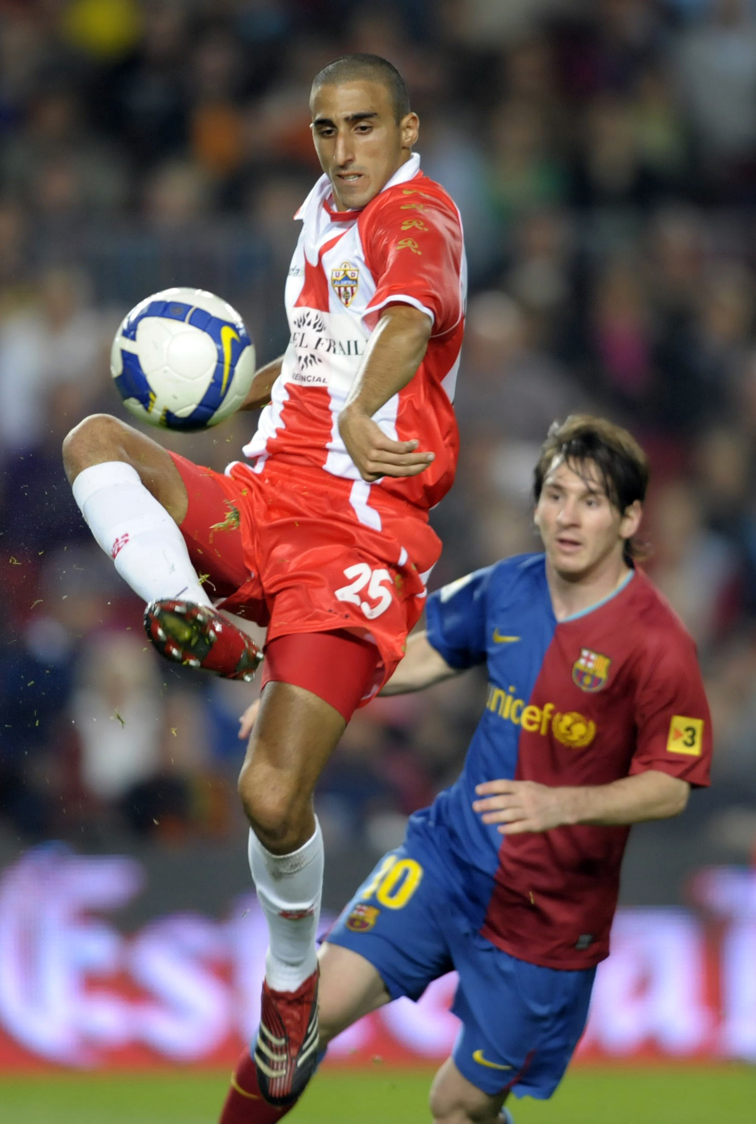 Barcelona's Lionel Messi, from Argentina, right, duels for the ball with Almeria's Hernan Dario during their Spanish league soccer match at Camp Nou S...