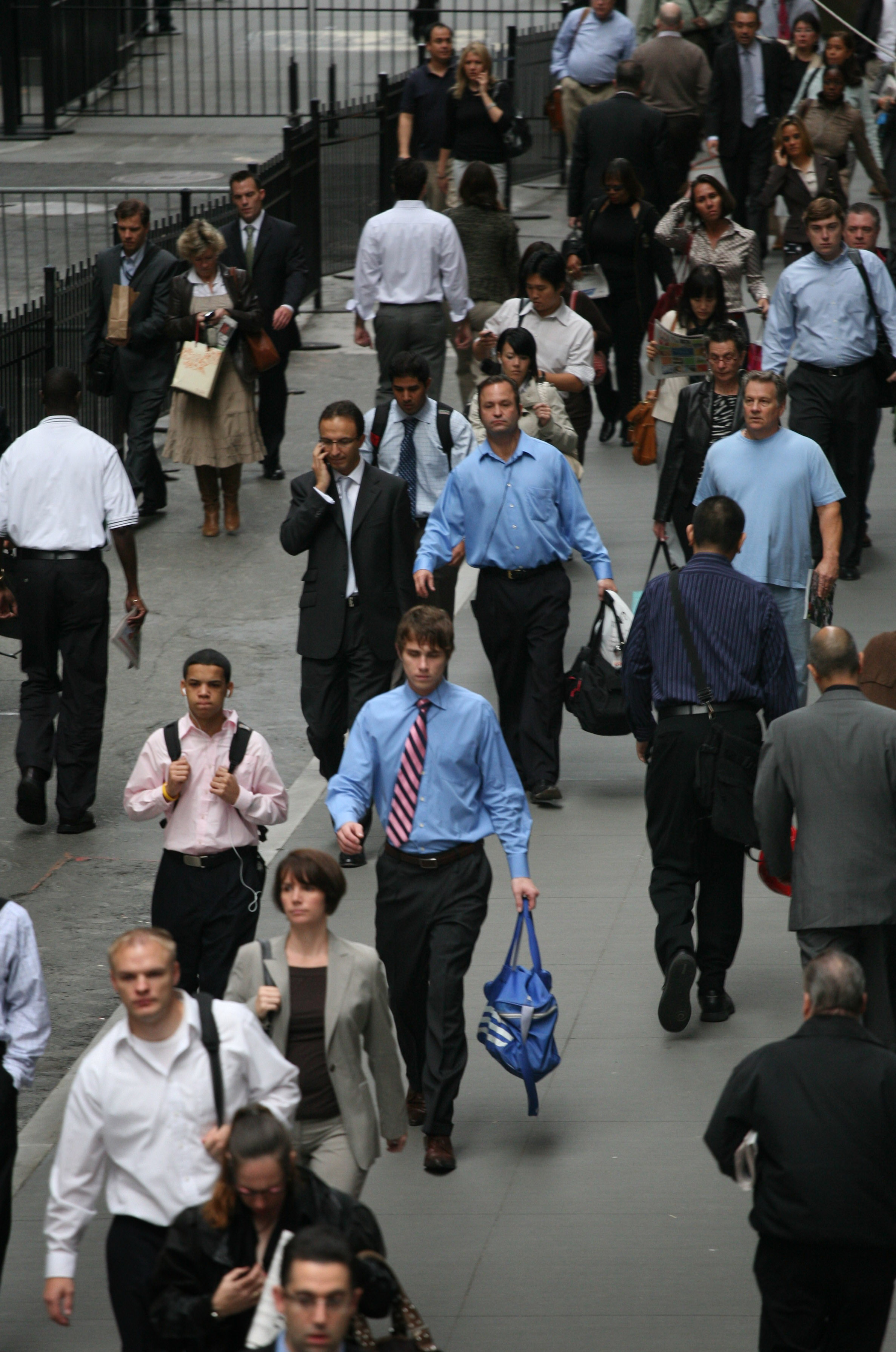 In this Sept. 30 file photo, people walk to work on Wall St., in New York, New York.