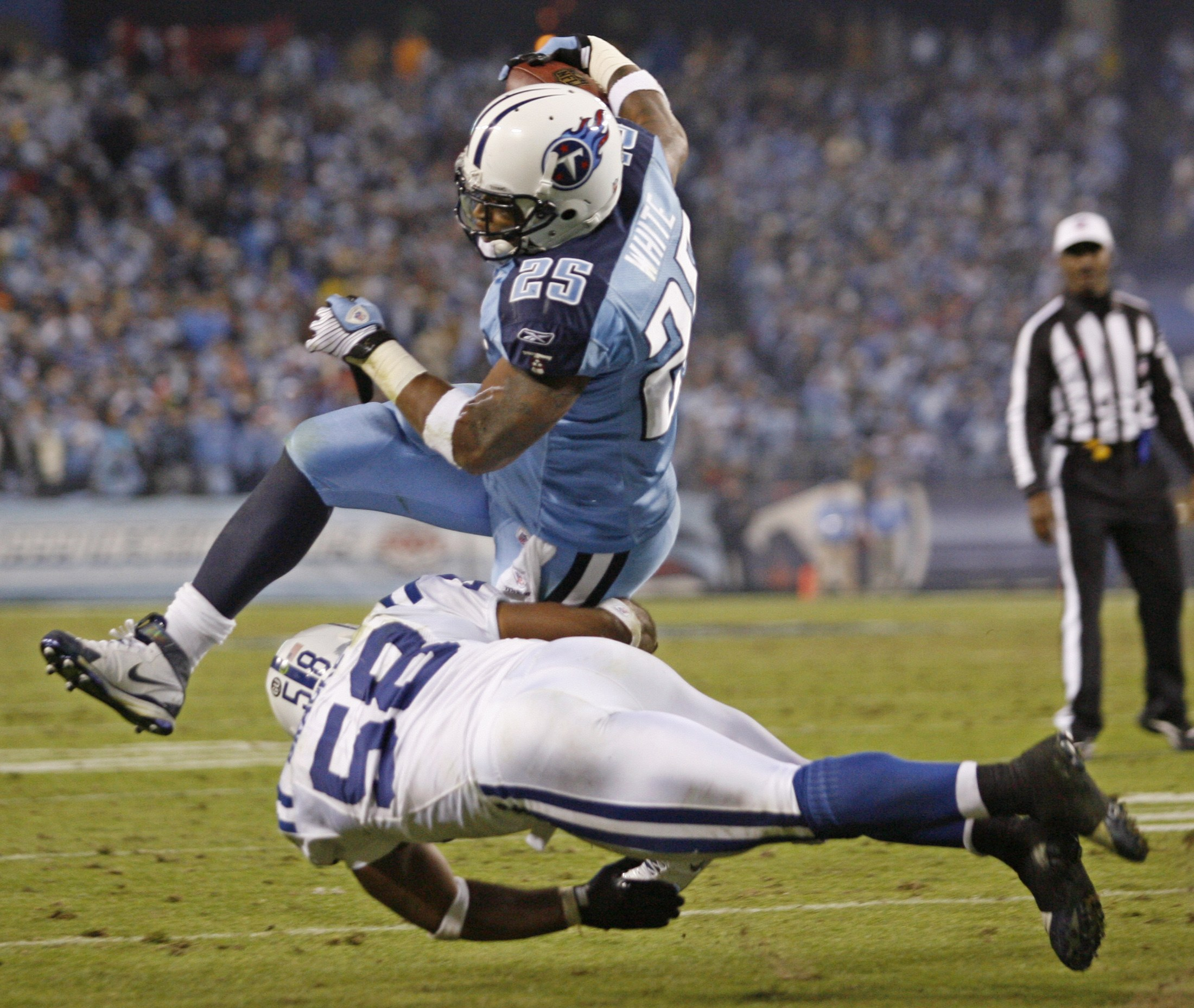 Tennessee Titans running back LenDale White leaps over Indianapolis Colts linebacker Gary Brackett to score during the second half of their NFL footba...