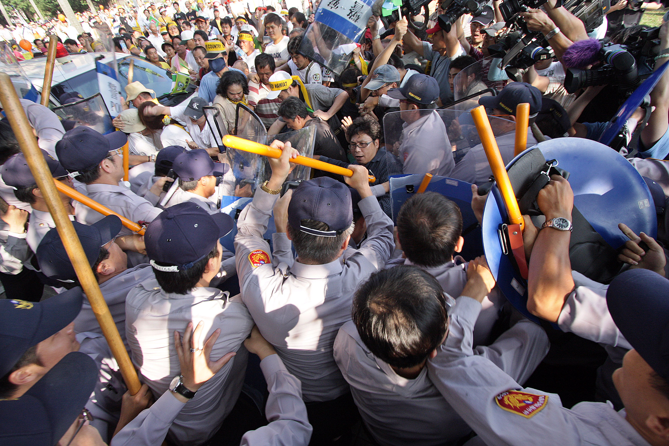 The crowd and police fight after protesters broke a barbed-wire defense line.