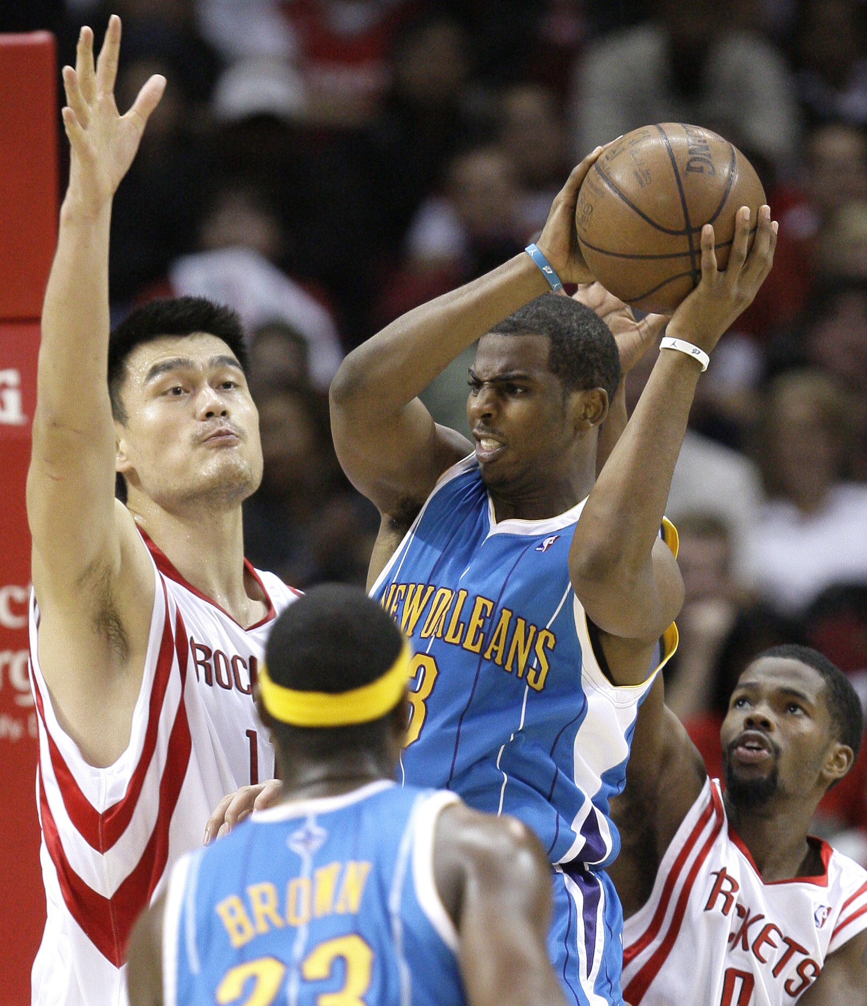 New Orleans Hornets' Chris Paul, center, looks to pass the ball as Houston Rockets' Yao Ming, left, of China, and Aaron Brooks, lower right, defend du...