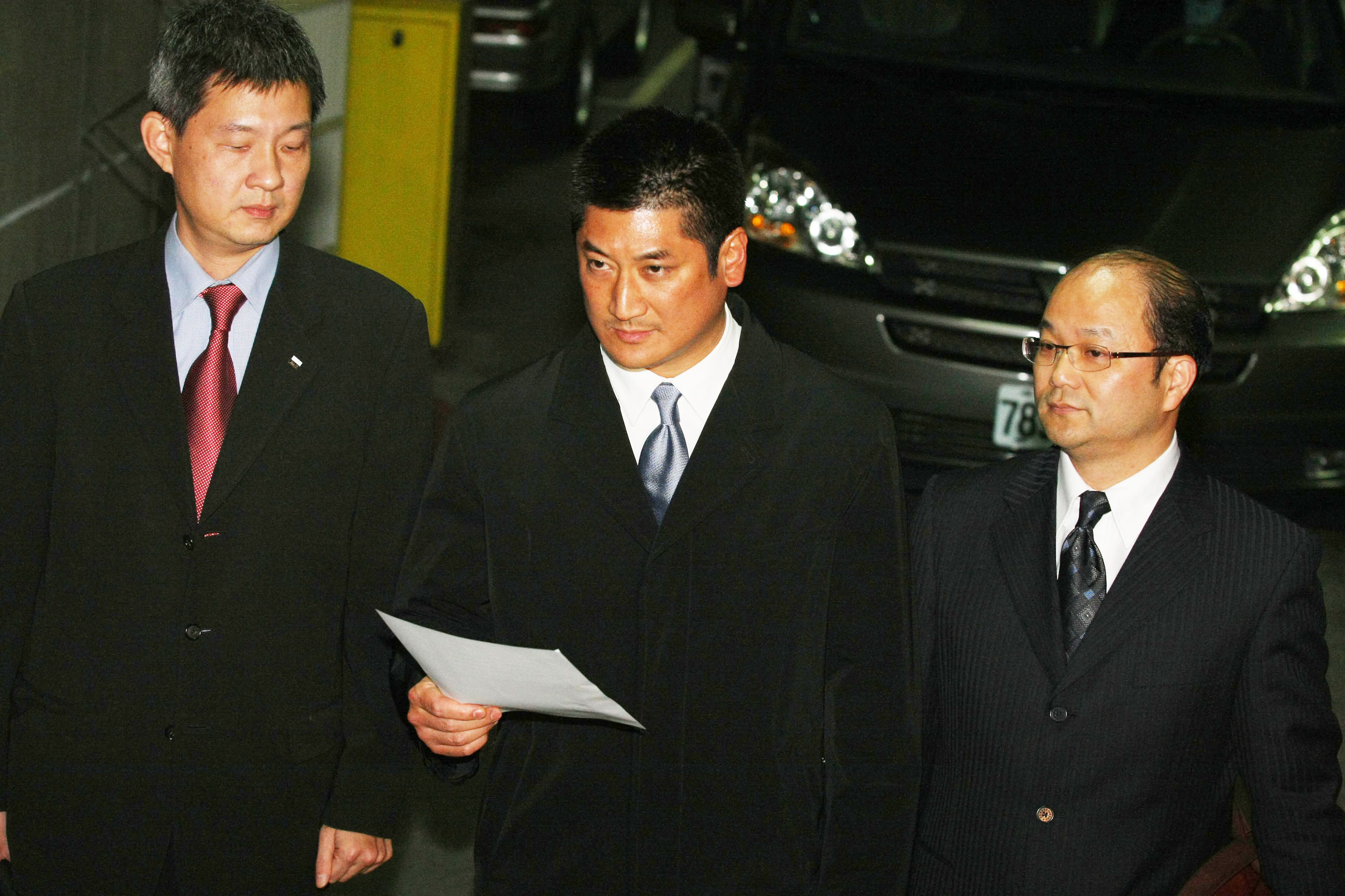 Former Chinatrust Financial Holding vice chairman Jeffrey Koo Jr., center, reads a statement following 12 hours of questioning by prosecutors on Monda...