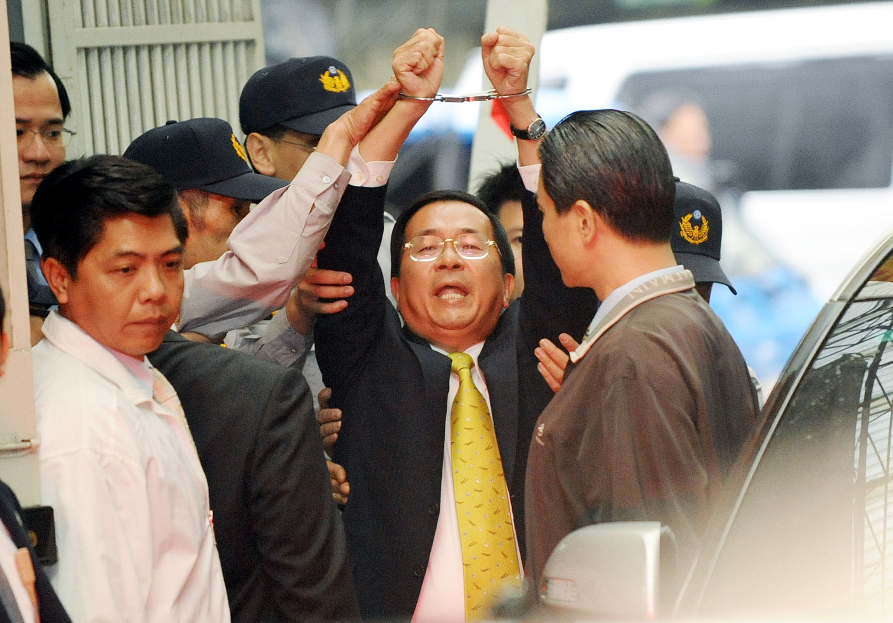 Chen Shui-bian raises his hands with handcuffs and called out political persecution after stepping out the Special Investigation Group.  The police so...