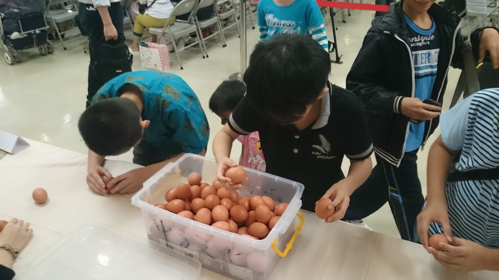Children stand eggs on the table.