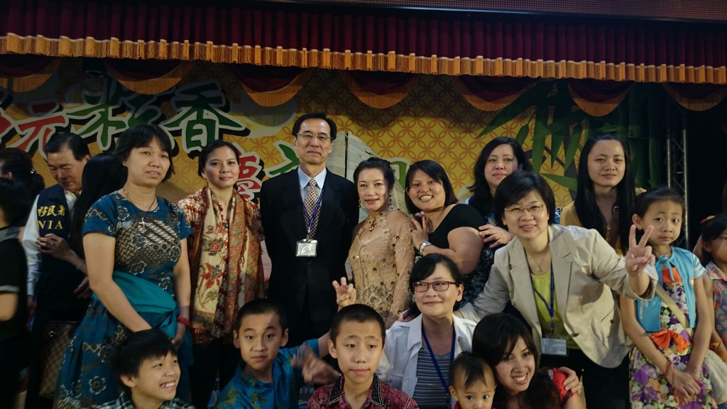 The Director-General of NIA Mo Tien-hu (central) takes a photo with new immigrants.