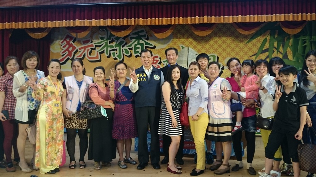 The deputy Director- General Ho Jung-chun (central) takes a photo with new immigrants.
