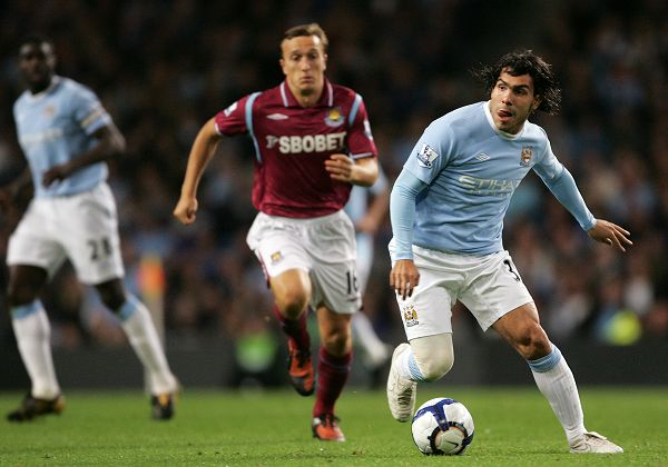 Manchester City's Carlos Tevez, right, gets away from West Ham's Mark Noble during their English Premier League soccer match at City of Manchester Sta...