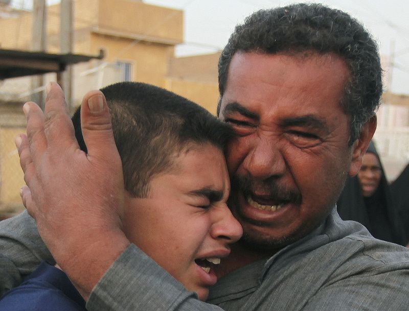 Family members of a man who was killed in a suicide bombing grieve at his funeral in Baghdad, Iraq on Monday. A pair of suicide car bombings Sunday de...