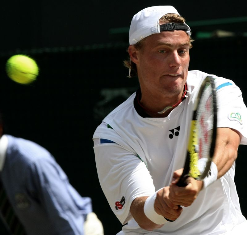 Lleyton Hewitt of Australia returns the ball to men's number one seed Roger Federer of Switzerland in their match at the Wimbledon tennis championship...