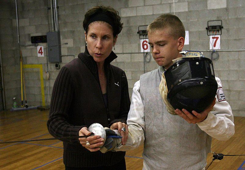 Head coach Rebecca Schneider (left) instructs Ezekiel Lough, 15, at Olympia Fencing.