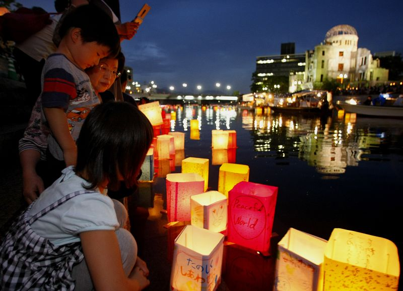 A family releases a paper lantern in the Motoyasu River with the backdrop of the Atomic Bomb Dome in Hiroshima, Japan on Aug. 6 as the city marked the...