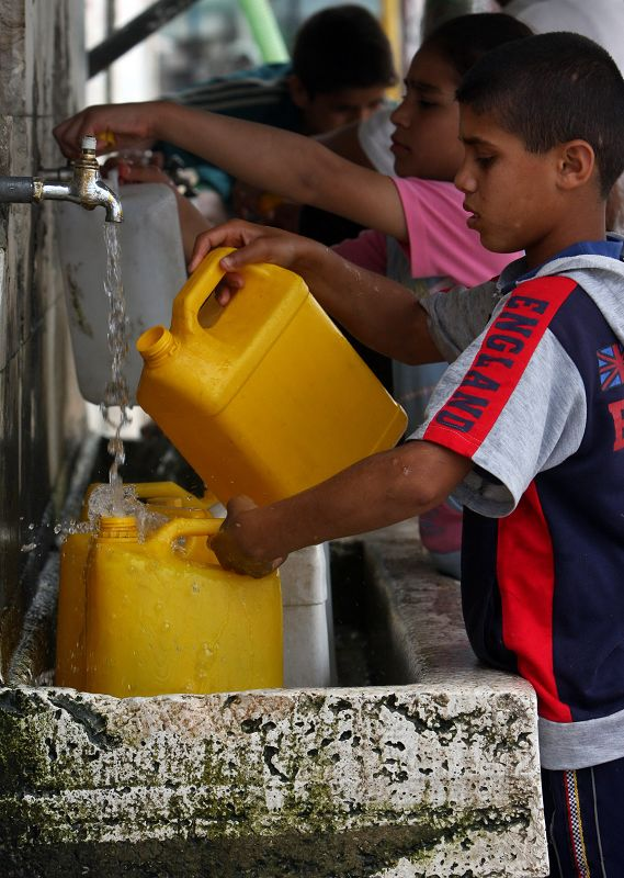 Palestinians fill canisters with water in Khan Younis refugee camp, southern Gaza Strip in this May 2008 file photo.