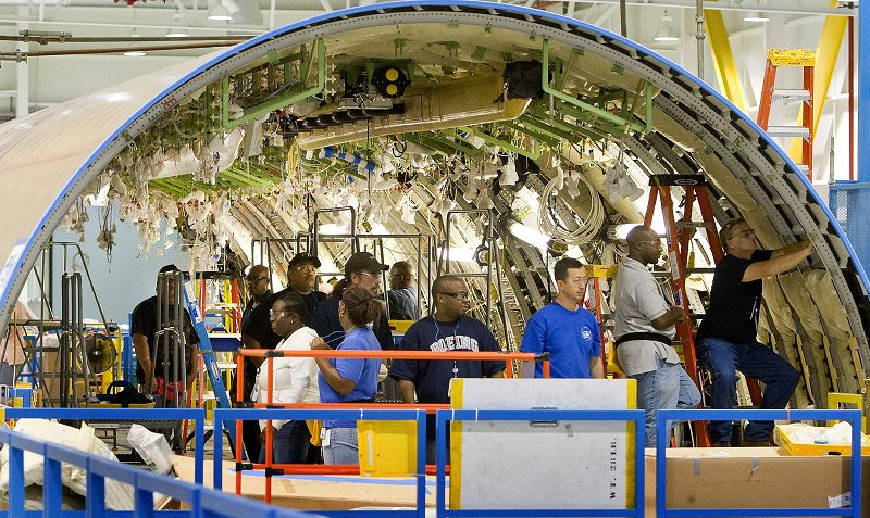 At Global Aeronautica's Charleston, South Carolina, factory, which is half-owned by Boeing, workers install wiring and insulation blankets in the cent...