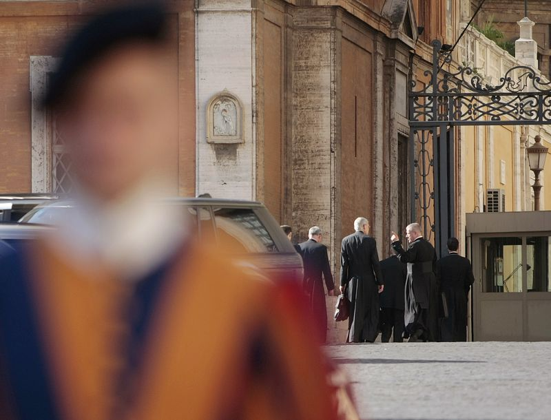 A Vatican Swiss guard stands outside an entrance to the Holy See as some priests background right, enter for a meeting.