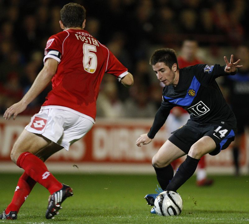 Manchester United's Zoran Tosic, right, keeps the ball from Barnsley's Stephen Foster during their English League Cup soccer match at Oakwell Stadium ...