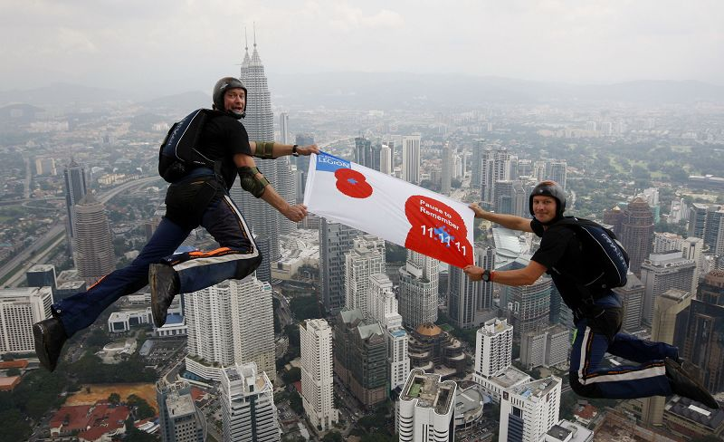 Two members of the British Armed Forces, Major Alastair Macartney, right, and compatriot Corporal Deane Smith leap from the Menara Kuala Lumpur Tower,...
