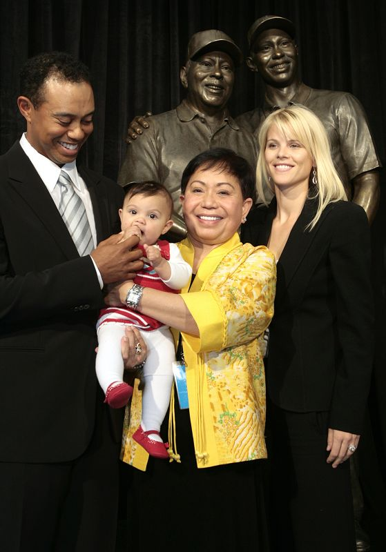 Tiger Woods, left, smiles as he stands with his daughter Sam, left to right, mother Kultida, and wife Elin Nordegren, next to a bronze statue bearing ...