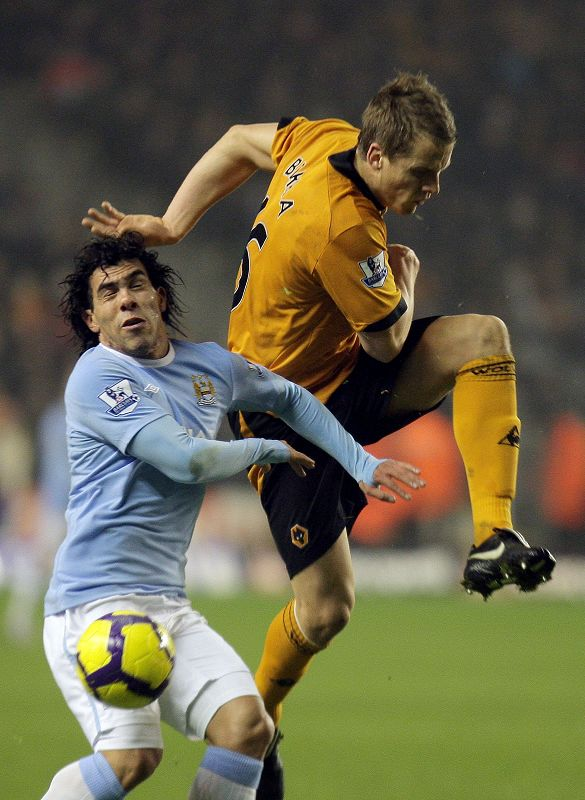 Manchester City's Carlos Tevez, left, competes for the ball with Wolverhampton Wanderers Christophe Berra during their English Premier League soccer m...