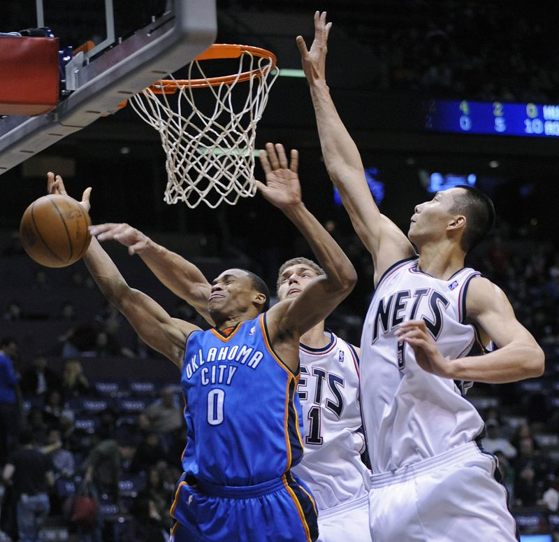 New Jersey Nets center Brook Lopez slaps the ball from Oklahoma City Thunder guard Russell Westbrook (0) as Yi Jianlian, right, of China, helps out on...