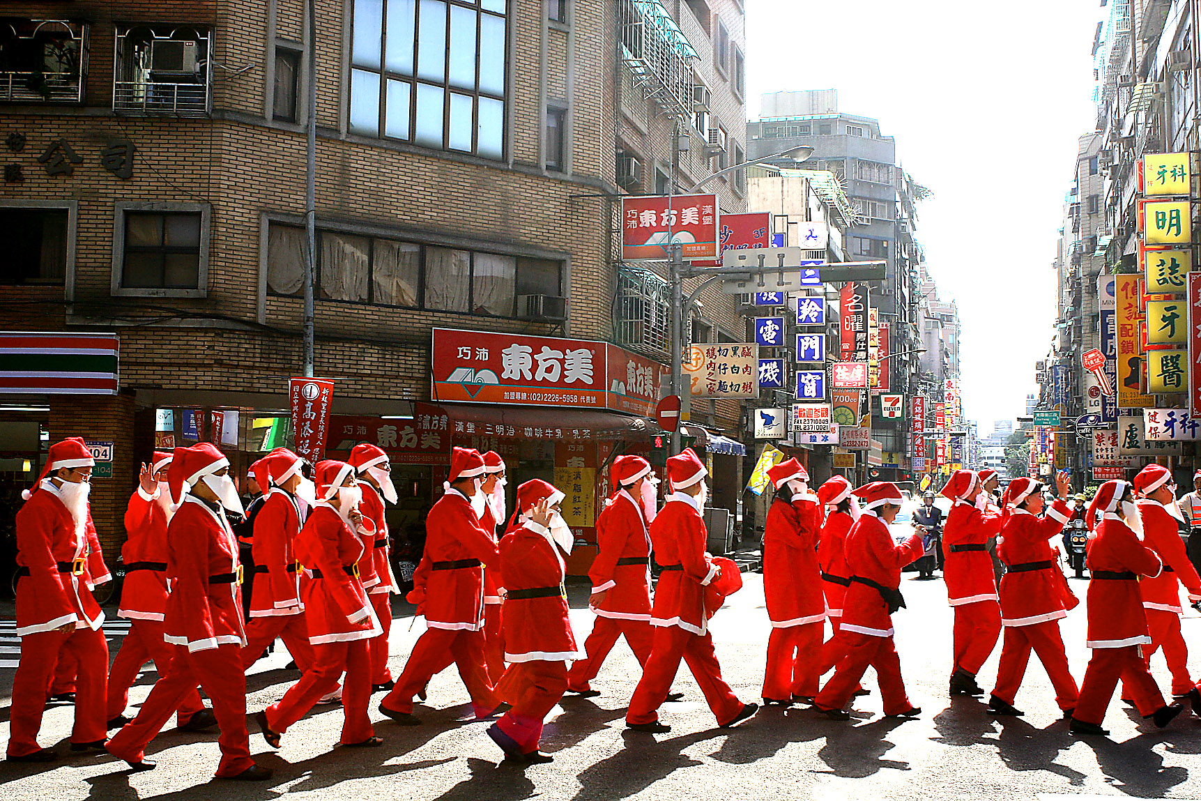 Church members who dress up as Santa Claus walk pass an old neighborhood in Hsimending, Taipei, December 24, 2006.