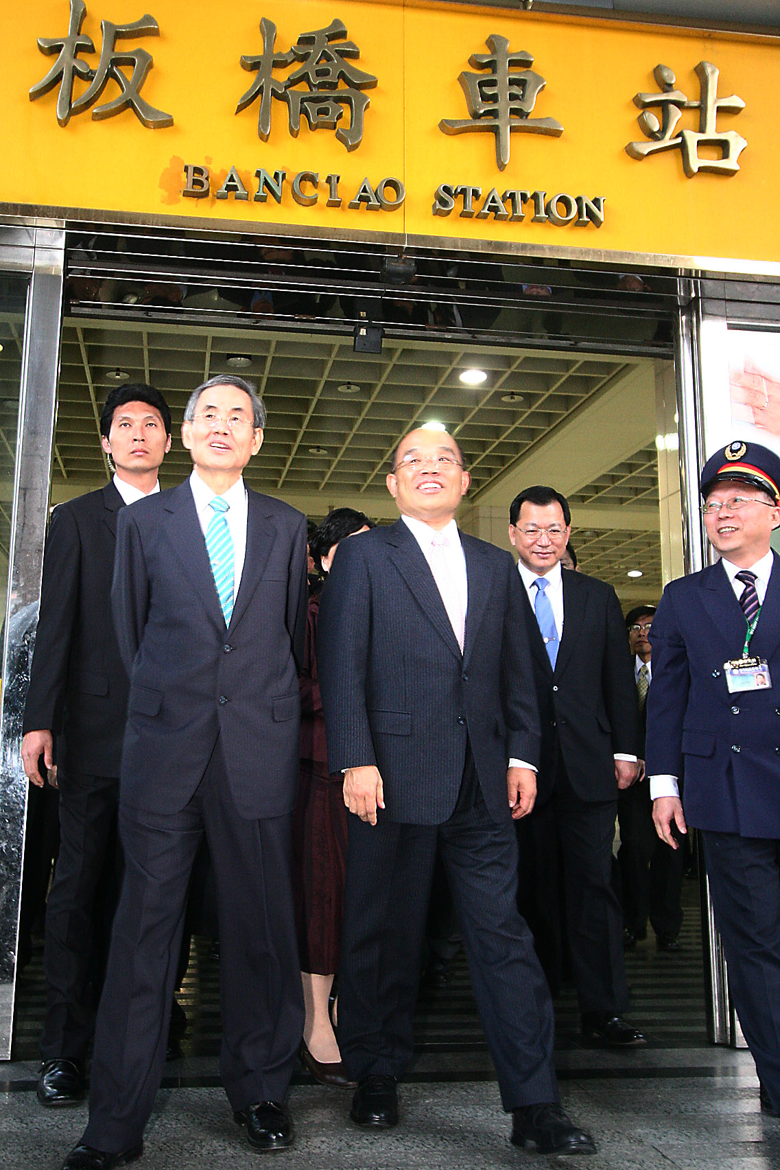 Premier Su Tseng-chang, center, and Minister of Transportation and Communications Tsai Duei, center left, step out of Banciao Station after riding the...