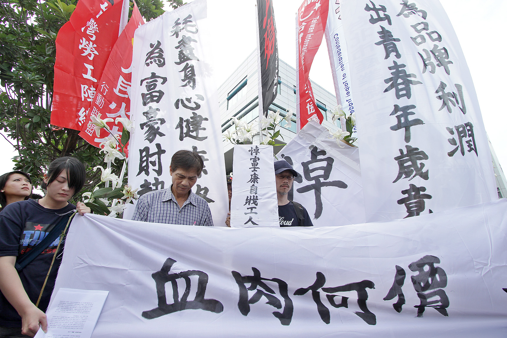 Labor activists pray during a protest held in front of the Foxconn headquarters in  Tucheng, Taipei County, on May 28, 2010, to urge the company to i...