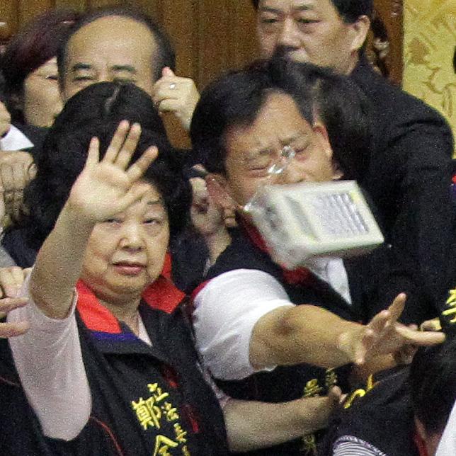Legislator Wu Yu-sheng, right, gets hit by a timing machine during a fight at the Legislative Yuan on July 8, 2010.