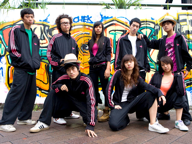 A 17-year-old troupe of street dance, Undergradu-Eight, pose in front of a graffiti wall.  Photo Courtesy of Flash Forward Entertainment