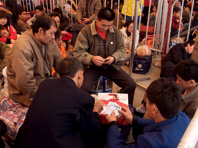 Migrant workers from Last Train Home released in 2009 play poker while waiting for their train home.  Photo Courtesy of CNEX
