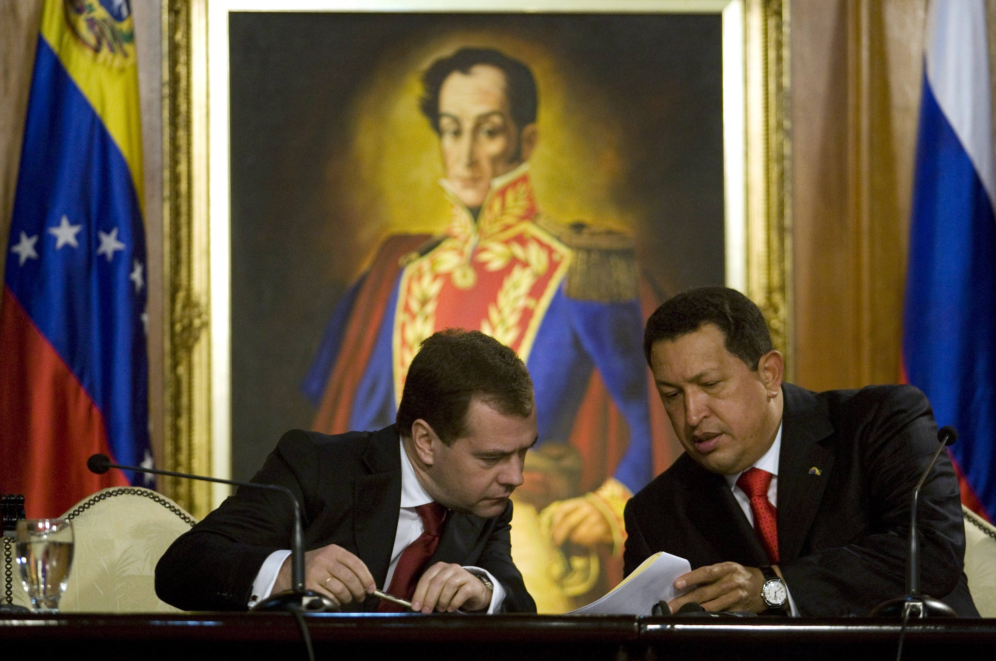 Venezuelan President Hugo Chavez, right, and his Russian counterpart Dmitry Medvedev sign agreements at Miraflores Palace in Caracas, Venezuela on Wed...