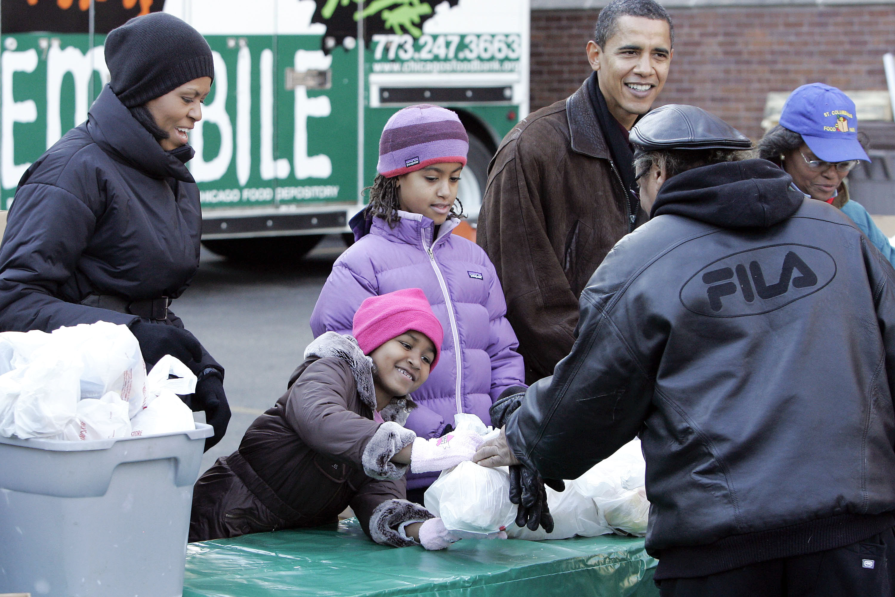 U.S. President-elect Barack Obama, right, helps distribute bags of food to residents with his wife Michelle, left, and daughters Sasha, second from le...