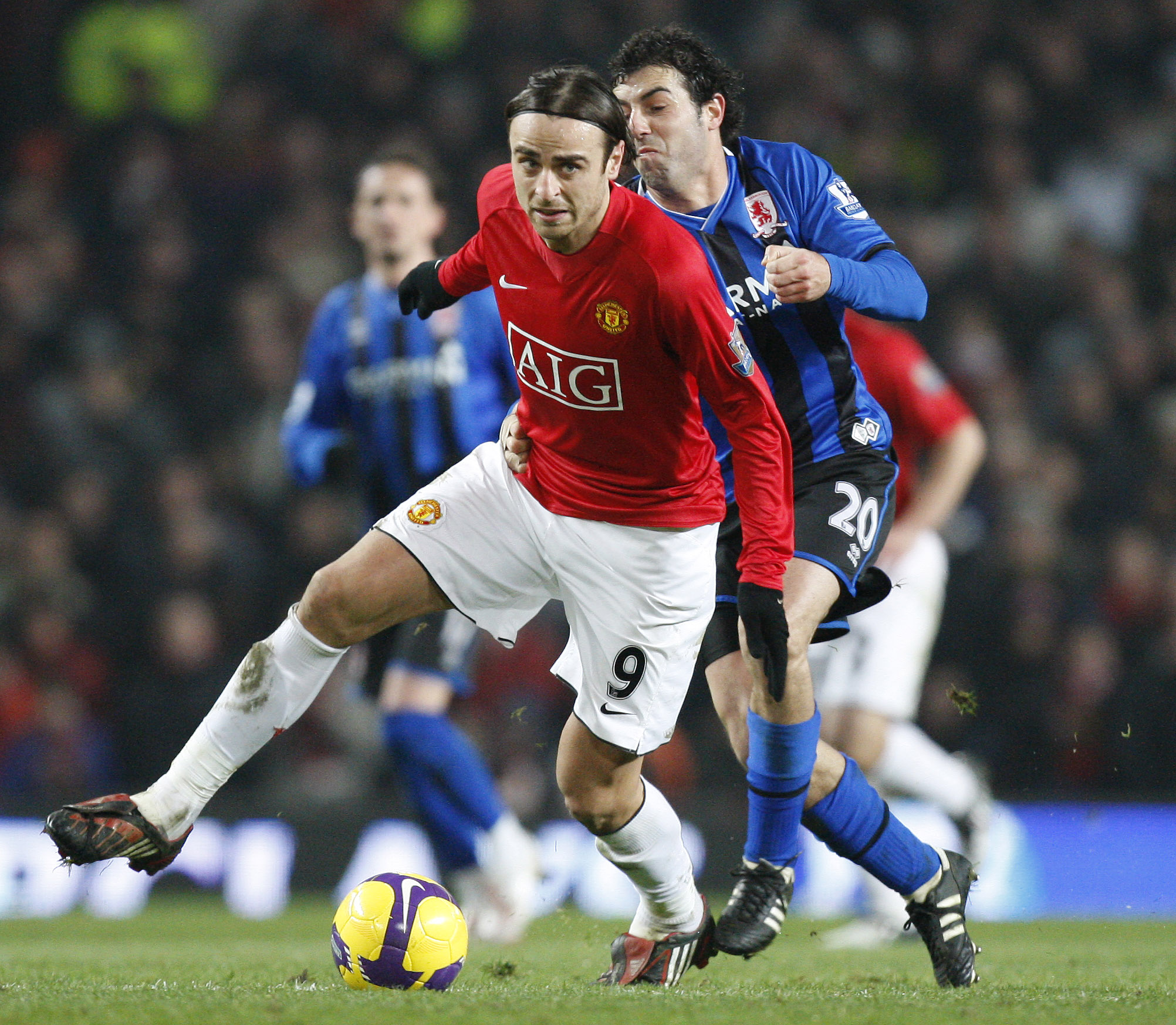 Manchester United's Dimitar Berbatov, left, keeps the ball from Middlesbrough's Julio Arca during their English Premier League soccer match at Old Tra...