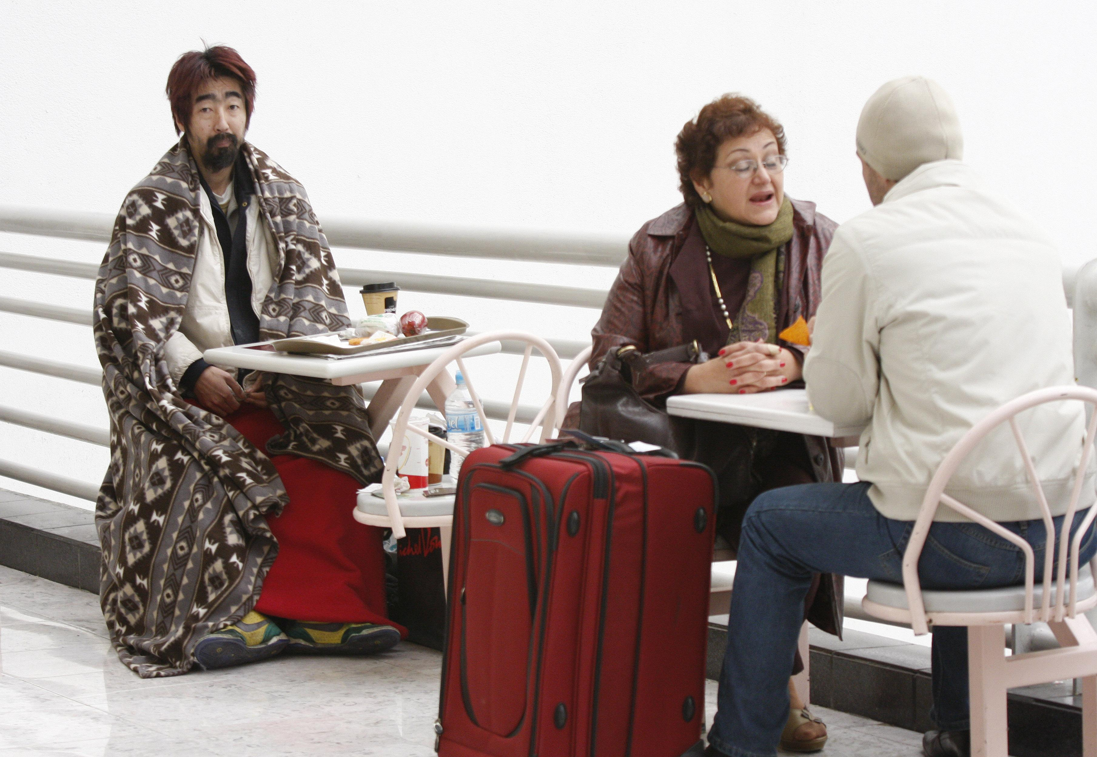 Hiroshi Nohara, of Japan, left, sits in Mexico City's main international airport, Mexico on Nov. 27.