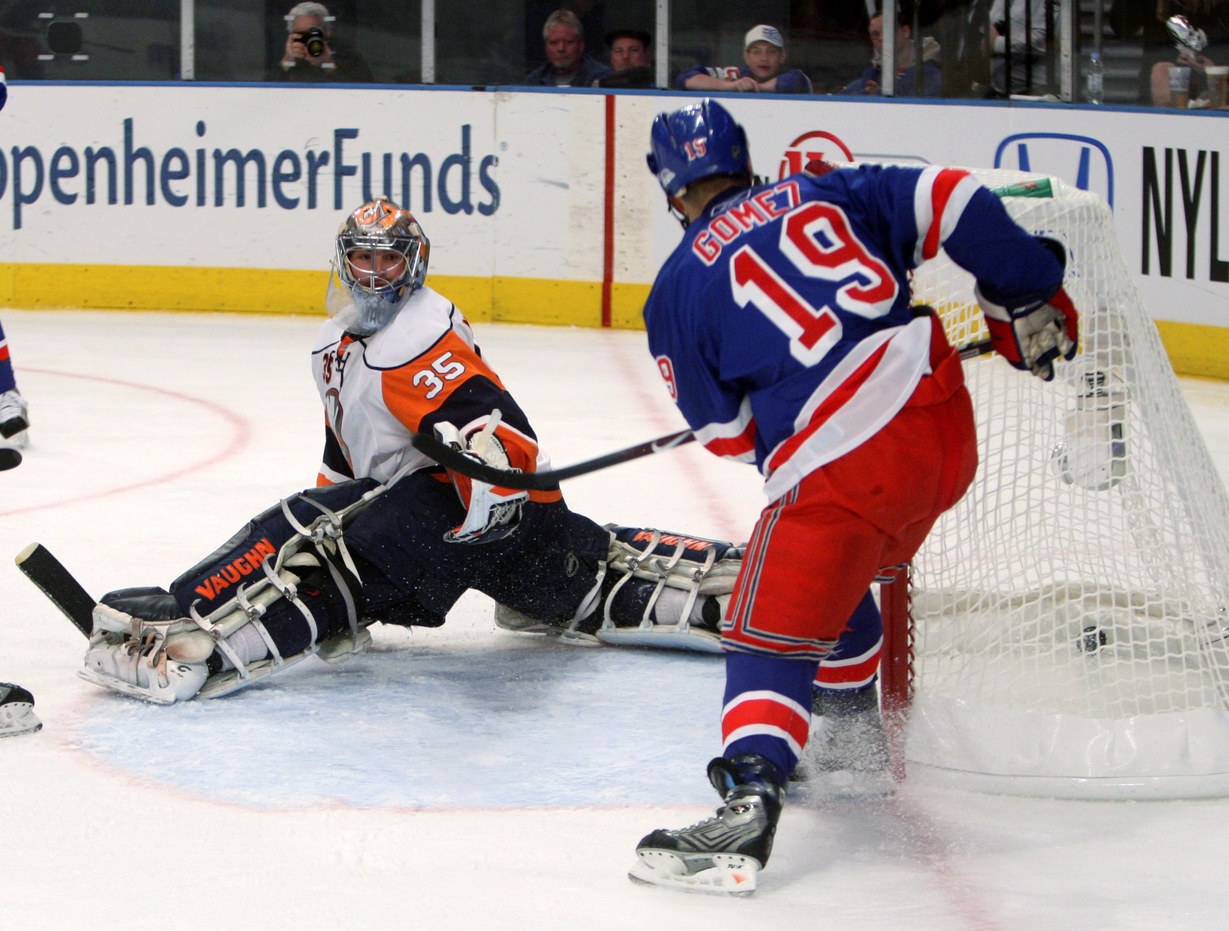 New York Islanders goalie Joey MacDonald, left, watches the puck get tapped in behind him by New York Rangers' Scott Gomez during the second period of...